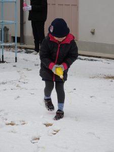 雪の上に女の子がペットボトルに入った絵の具で絵を書いてる