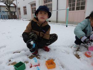雪の上に男の子がペットボトルに入った絵の具で絵をかいてる